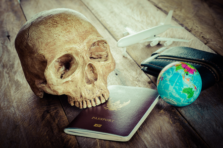 underestimate: skulls on the passport on wood table - concept is getting dangerous. Do not be careless