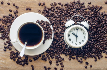 lethargy: Coffee and coffee beans are placed near the alarm clock - concept articles useful as well