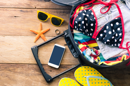 Clothing travelers , wallet, smart phone devices, on a wooden floor in the luggage ready to travel.