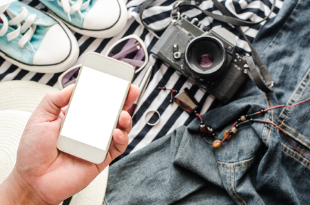 close up of traveler hands with blank smartphone screen and map concept planning travel Foto de archivo