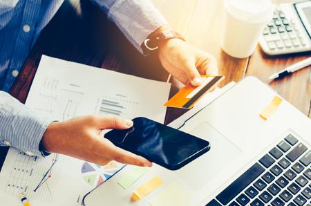 Hombre de negocios la celebración de teléfono inteligente y el trabajo con el ordenador portátil en la tabla y la carta de inversión de análisis en la oficina. Concepto de trabajo de negocios.