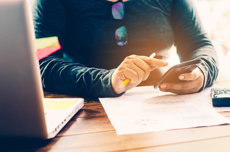 co: Businessman holding smart phone and working with laptop on the table and analyzing investment chart working in office. Business work concept.