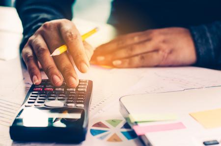 Hombre de negocios están trabajando con una calculadora y un ordenador portátil. En el concepto de negocio de oficina Foto de archivo