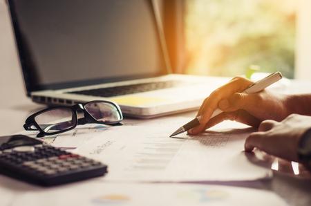 Hombre de negocios la celebración de papeleo en la tabla y el análisis de la carta de inversión que trabajan en la oficina. Concepto de trabajo de negocios.