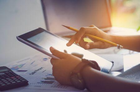Hombre de negocios la celebración de Tablet y el trabajo con el ordenador portátil en la tabla y la carta de inversión de análisis en la oficina. Concepto de trabajo de negocios.