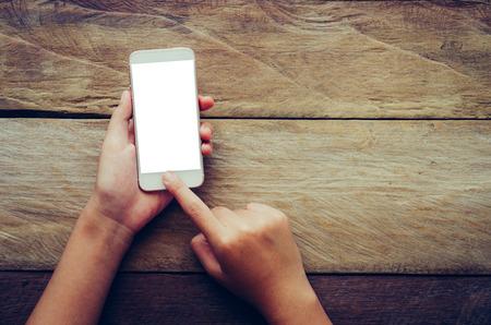 Mano sosteniendo teléfono inteligente aislado en fondo de madera