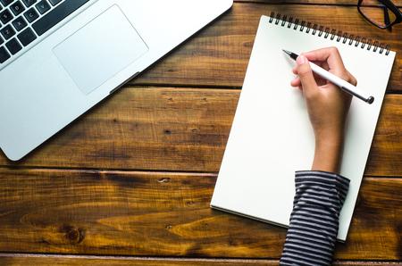 Las manos están escribiendo en un cuaderno en suelo de madera Foto de archivo