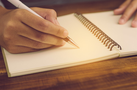 Primer plano de la mano de la mujer escrito en papel Foto de archivo