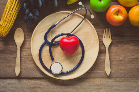 Healthy concept, fruit and ear doctor on wood background