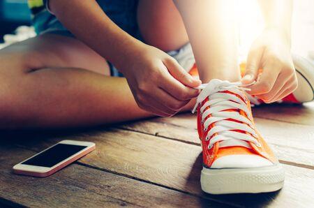 Manos de un cordones de zapatos de mujer joven y rojo sentado en el pavimento de madera en la mañana Foto de archivo
