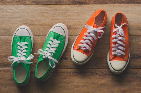 Zapatillas rojas y verdes en suelos de madera - estilo de vida Foto de archivo