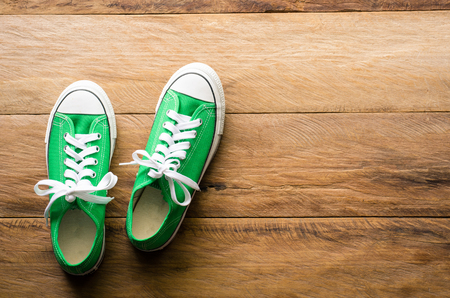 Green sneakers on wooden floors.-lifestyle