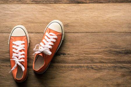 Zapatillas rojas en suelos de madera. Foto de archivo