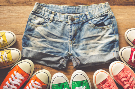 Short jeans for teenage girls and sneakers on wooden floors. Stock Photo