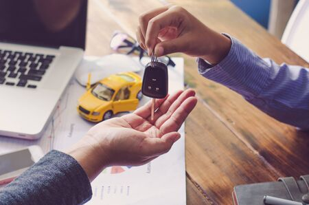 Real showroom car agents will give keys to tenants after the contract is completed. Stock Photo