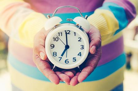 Las manos que sostienen un reloj le dan al concepto un tiempo.