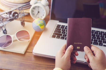Travelers hold a passport are planning a trip for the holidays on laptop background - concept prepare to travel Foto de archivo