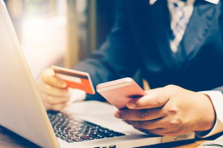 Hombre de negocios usando tarjeta de crédito y teléfono inteligente con una computadora portátil para comprar en línea
