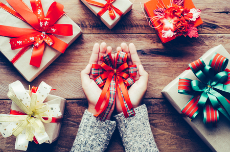 Hand are wrapping gifts for a special festival on a wooden table.