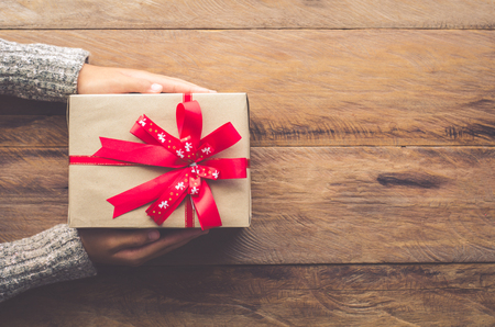 Woman holding gifts for special moments with special who on wooden floor.