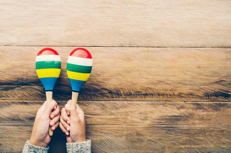 Hand holding Maracas on wooden floor. Foto de archivo
