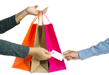 Customer paying for their order with a credit card in shopping mall. seller holding a shopping bag and returning the credit card for customer after payments