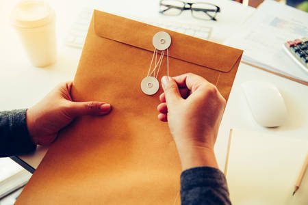 Businessmen are about to open a brown envelope containing business documents on a desk with office supplies