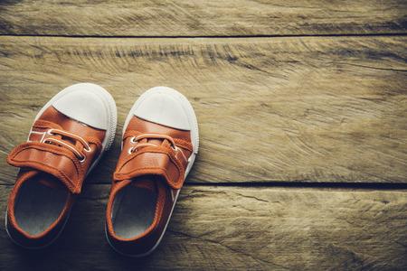 Zapatos rojos para niños en el piso de madera Foto de archivo