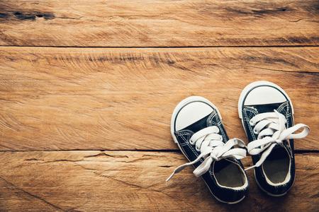 Black shoes for children on wooden floor Foto de archivo