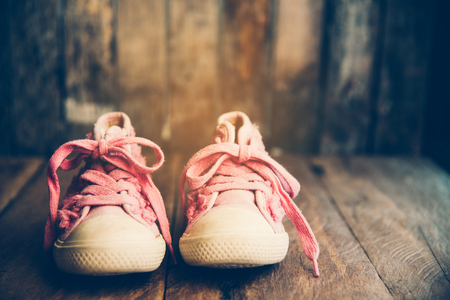 Pink shoes for children on wooden floor Foto de archivo