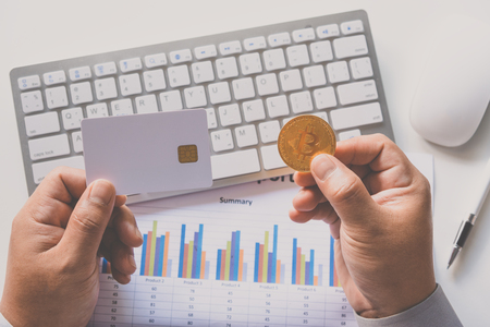 Hand holding Credit card with bitcoins with a laptop background and graphs of business functions - Business and investment alternatives.