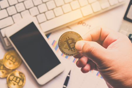 Man holding Bitcoin and background with Smart Phones, Laptops and Business Graphs - Concepts for Starting a Business and Investing