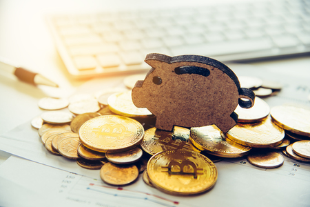 bitcoins are placed on the area with the sign of piggy bank overlaid on the area of the working table with a laptop. - The concept of saving money