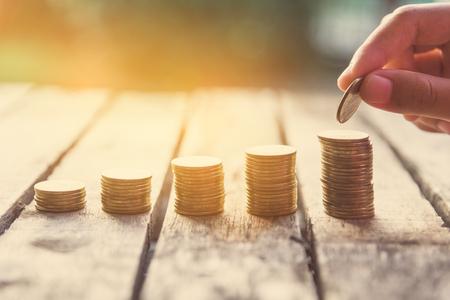 Hand putting money coin on each line rising - business saving money concept.  Foto de archivo