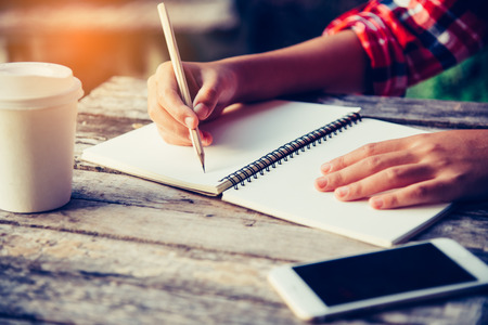 The hand is writing a notebook with a pencil and a cup of coffee, a smartphone placed on a wooden desk in an office with golden light.