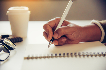 The womans hands are writing note and coffee cup in open spect and light gold in morning