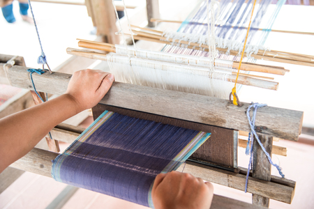 The hand of a weaver is woven with a hand-woven machine.