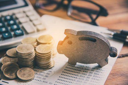 Coins are placed on the area with the sign of piggy bank overlaid on the area of the working table with a laptop. - The concept of saving money