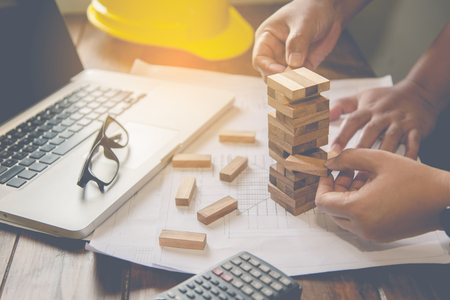 Hand for engineer safety for the game drew to a wooden block from the tower. Concept engineer risks in the job. Requires planning Meditation must be careful in deciding to reduce the risk in the job Foto de archivo