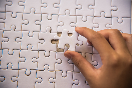 Handle a piece of white puzzles that are about to drop to get a complete worksheet - An attempt to succeed.  Stock Photo