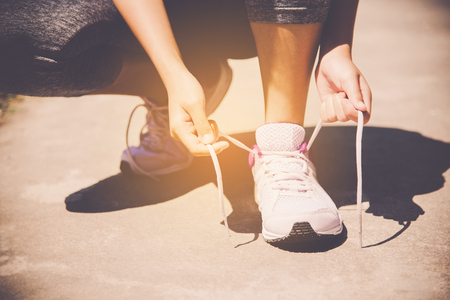 Hands of a young woman shoelace and sneakers. Shoes standing on the pavement of stones in the morning for for exercise