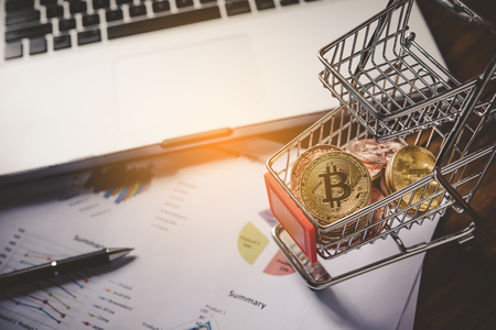 Bitcoin in mini shopping cart on table for work and laptop for work to shopping online concept  Stock Photo