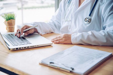 The doctor is sitting worker on laptop Stock Photo
