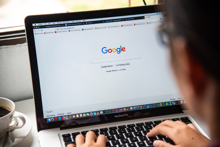 LAMPHUN, THAILAND - July 8, 2018: Woman is typing on Google search engine from laptop. Google is the largest and most popular Internet search engine in the world.