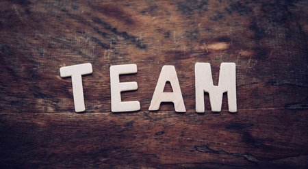 The word TEAM is arranged from a wooden letter placed on a wooden floor. Stock Photo