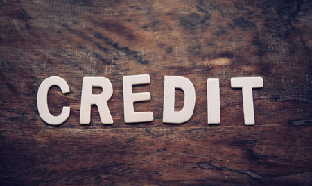 The word CREDIT is arranged from a wooden letter placed on a wooden floor. Stock Photo