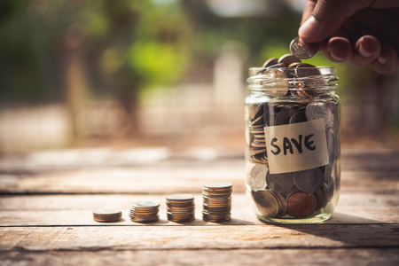 Hand  putting coins in jar with money stack step growing growth saving money,  finance and investment Concept Stock Photo