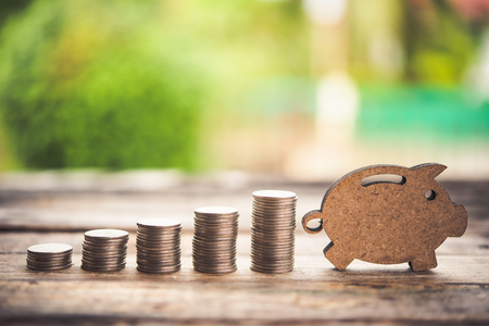 The coins are stacked and wooden blocks are pig on the wooden floor. - Savings ideas for increasing volume. Stock Photo