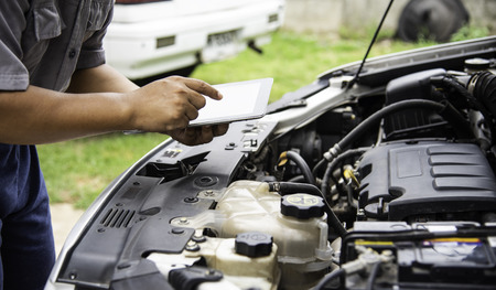 Professional mechanic checking car engine search for data with tablet