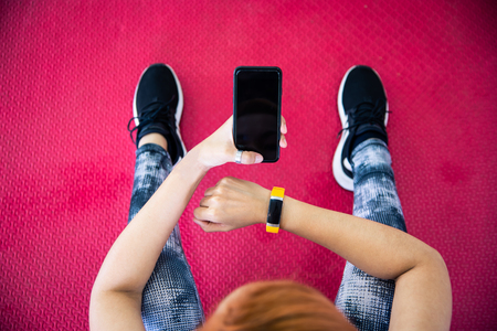 Woman in fitness clothing using smartphone. in gym for exercise